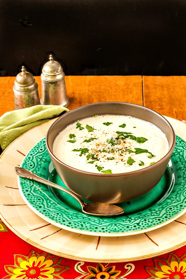 A brown bowl of cream of cauliflower soup on a green plate.