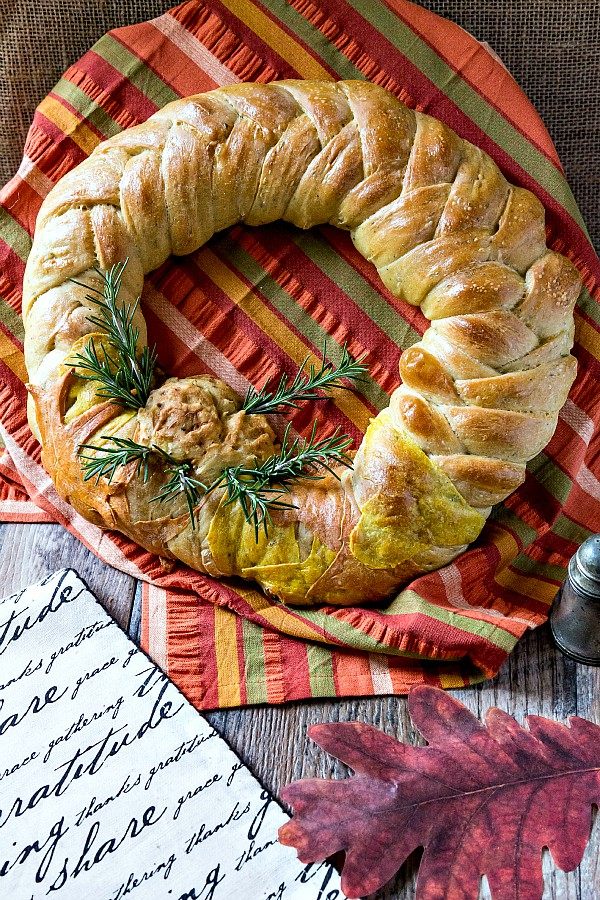 A braided bread wreath decorated with rosemary on a striped napkin,