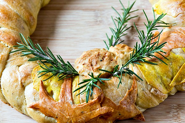 Close up of the pinecone, leaf decoration in dough and rosemary sprigs on a decorative Thanksgiving bread.