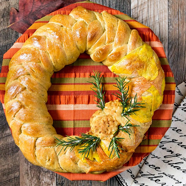 A braided wreath bread against a wooden background.