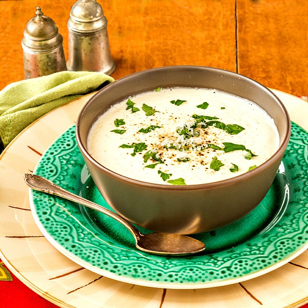 A bowl of cream of cauliflower soup on a green plate with chopped herbs for garnish.
