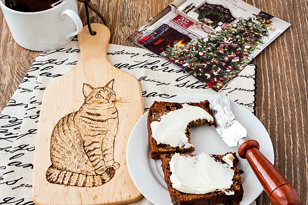 A cloth napkin and a small cutting board with an image of a cat and a plate with a slice of fruit cake with cream cheese on it. One bite is missing.