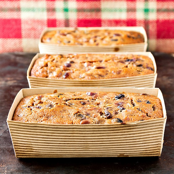 Three individual Alton Brown fruit cake in brown cardboard mini loaf pans on a brown surface with red and green plaid burlap in the background.
