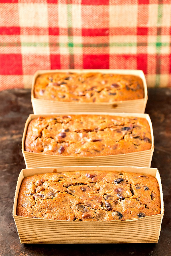 3 individual fruit cakes in cardboard loaf pans with red and green plaid burlap as the background.