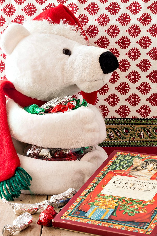image for chewy candy recipes: a white stuffed bear in a red Santa hat holding an armful of cocoa taffy wrapped in foil
