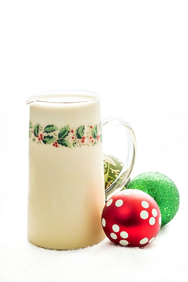 A glass pitcher decorated with holly, filled  with orange spiced eggnog, next to 3 Christmas ornaments.