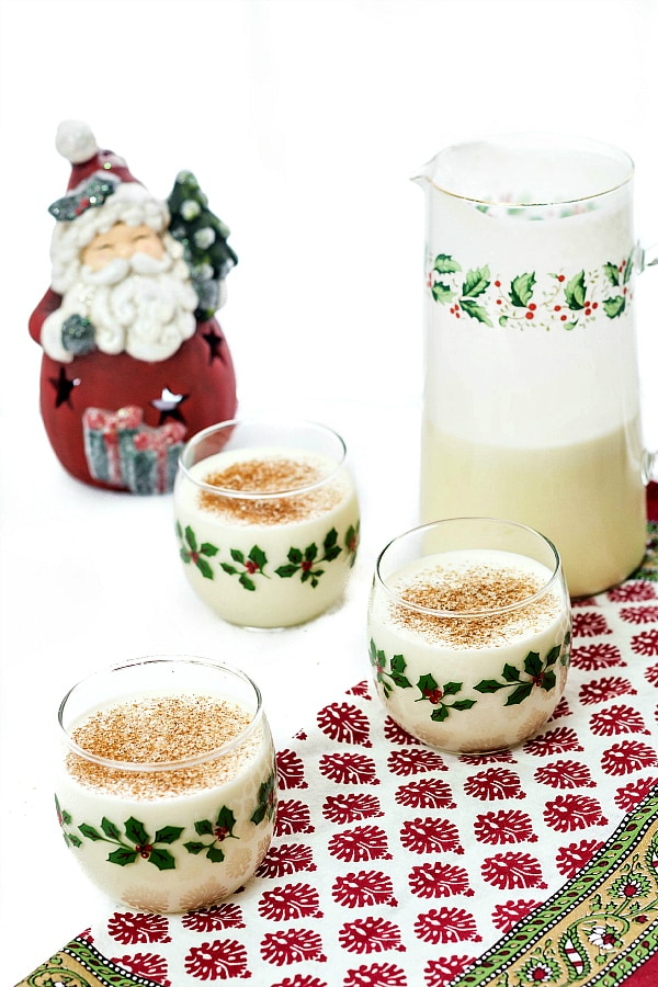 A half-empty pitcher of eggnog with three glasses of eggnog topped with nutmeg. All are decorated with holly. A Santa figurine is in the background.
