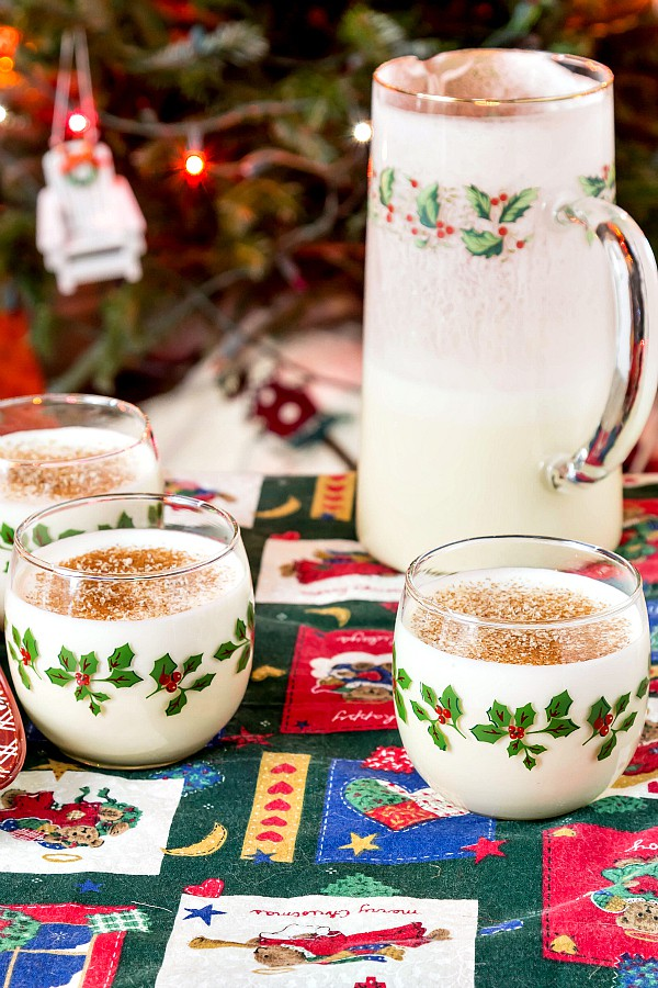 A pitcher and glasses of eggnog with a Christmas tree in the background.