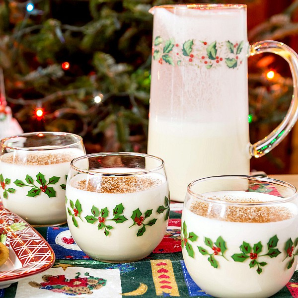 3 holiday glasses of eggnog, each sprinkled with nutmeg, with a pitcher of eggnog, all in front of a Christmas tree.