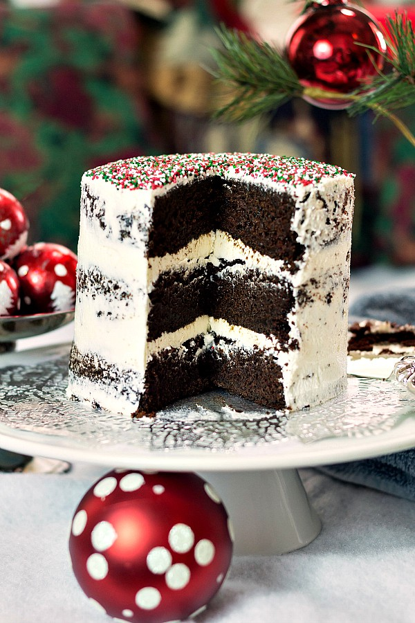 A vegan version of the Halloween chocolate cake decorated with white frosting and green and red sprinkles for Christmas.