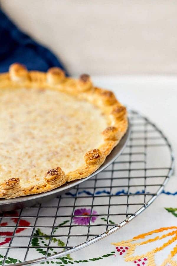 whole sugar cream pie in a metal pie pan on a colling rack