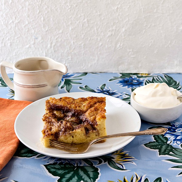 French toast casserole on a white plate with a pitcher of syrup and a small bowl of whipped cream