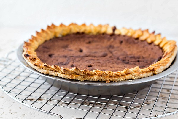 A whole chocolate chess pie in a metal pie pan cooling on a wire rack.