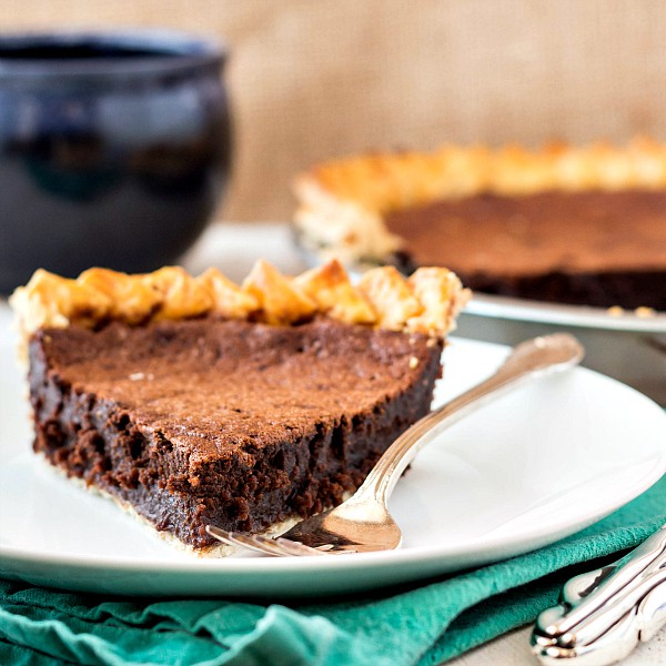 A slice of chocolate pie on a white plate with a silver fork ready for serving. The rest of the pie is in the background.