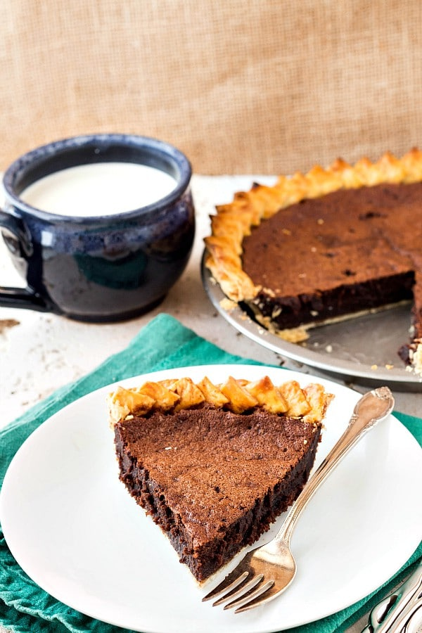 A slice of chocolate pie on a white plate with the rest of the pie in the background and a mug of cold milk.