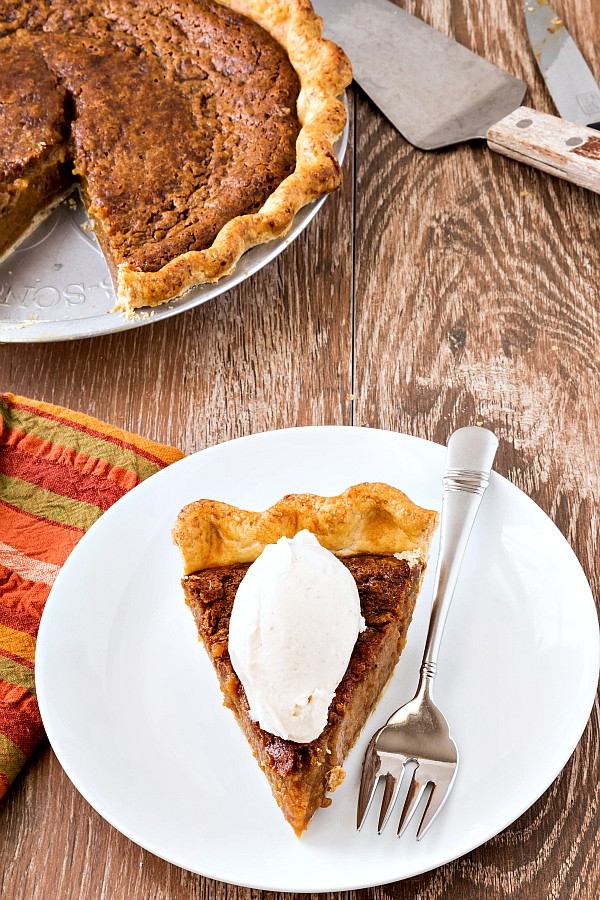 a piece of sorghum pie on a white plate with a fork and a quenelle of ice cream on top