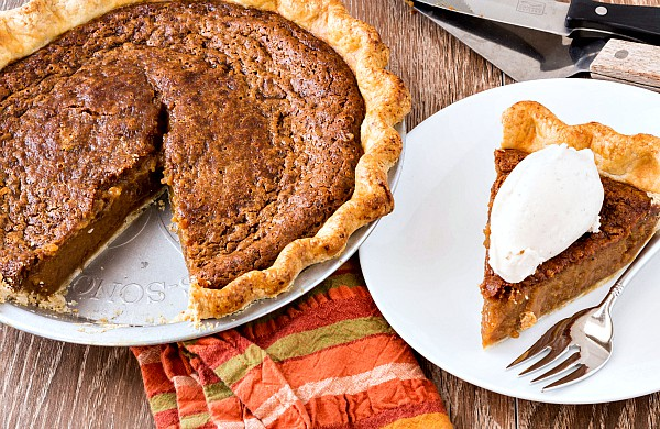 a pie with one slice out of it in a pie pan with the slice of pie on a white plate