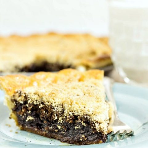 slice of dark shoofly pie with light streusel topping on a blue plate