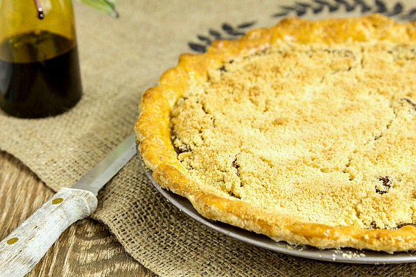 A whole baked shoo fly pie on burlap with a knife next to it, ready for serving.