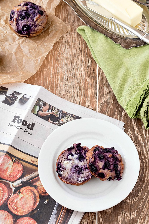 A split dairy free blueberry muffins on a white plate with a Sunday NY Times Food section.