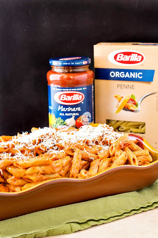 Creamy vodka sauce on pasta in a serving dish with a jar of pasta sauce and a box of pasta in the background,