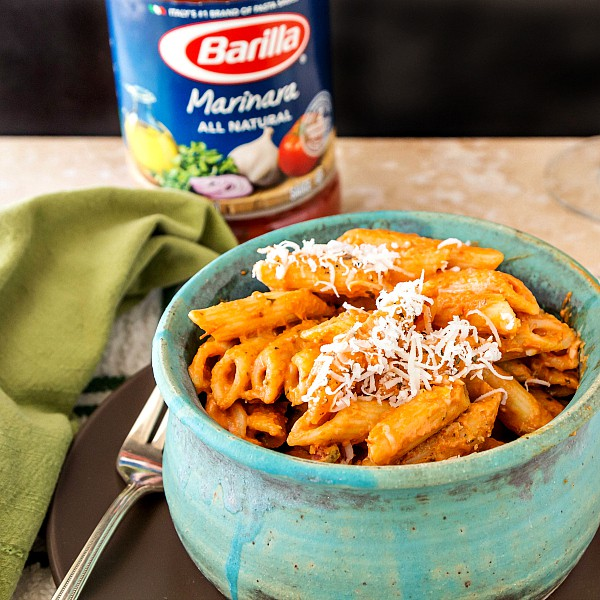 penne pasta in a creamy sauce in a blue bowl with a jar of pasta shot in the background