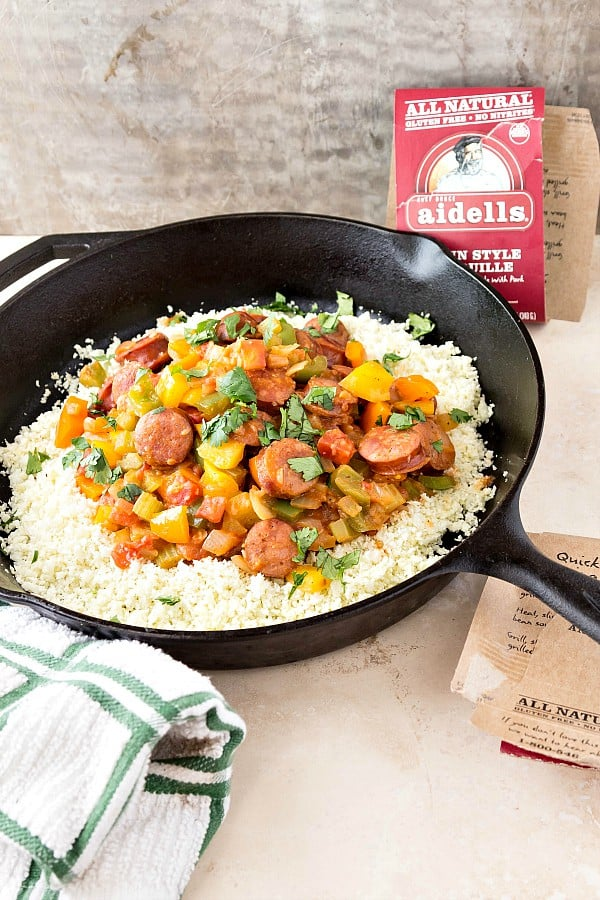 A skillet filled with cauliflower rice and Cajun sausage with peppers.