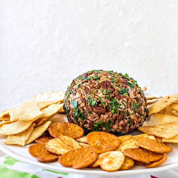 port wine cheese ball rolled in nuts and herbs on a platter with crackers