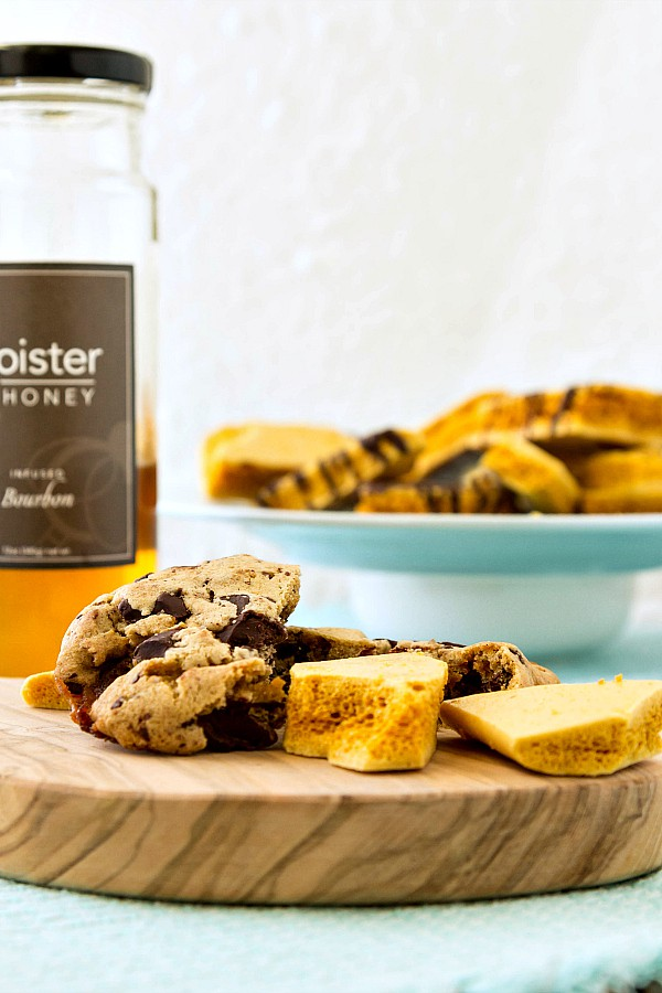 cookies and honeycomb candy on a wooden board with a jar of bourbon-infused honey and more honeycomb candy in the background