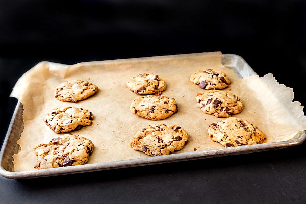A parchment lined baking tray with baked cookies on it.