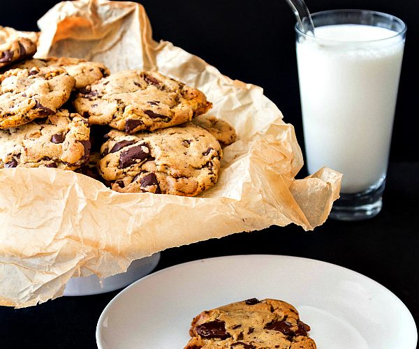 cookie on a plate with a basket of cookies and a glass of milk