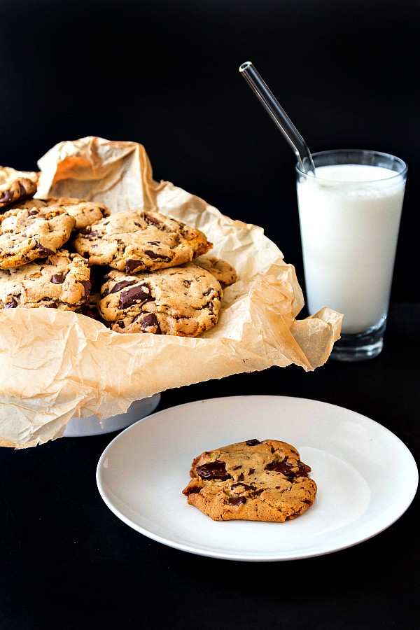 A plate of chocolate chunk cookies and a glass of milk with a glass straw in it. One cookie is on a single plate ready for serving.