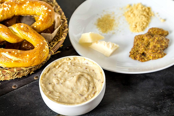 Thick beer cheese dip served wtih a basket of baked pretzels. A white plate of recipe ingredients are next to the serving.