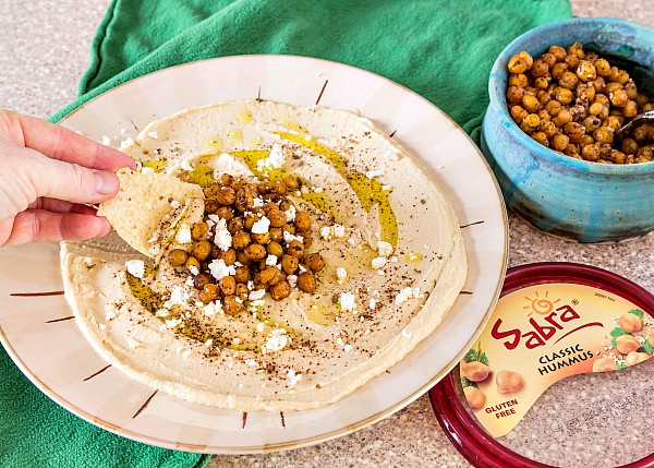 A plate of hummus with olive oil, chickpeas and za'tar, with a hand using a pita chip to scoop some up. Sabra hummus lid is next to plate, along with blue bowl of roasted chickpeas.