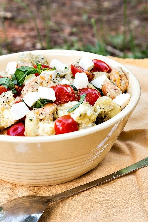 A large pottery bowl filled with tortellini caprese salad.