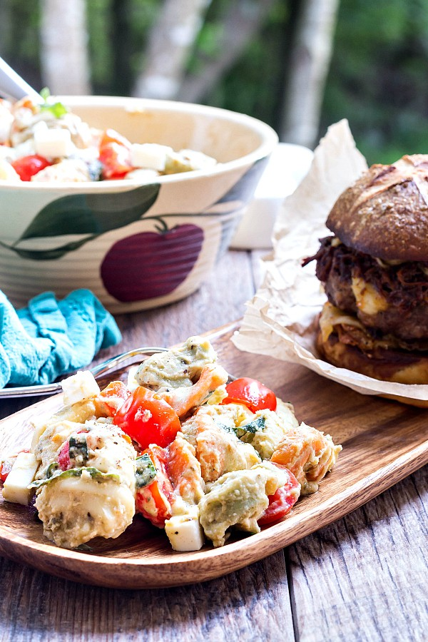 A serving bowl of tortellini caprese salad next to a wooden plate with a burger and serving of the salad.