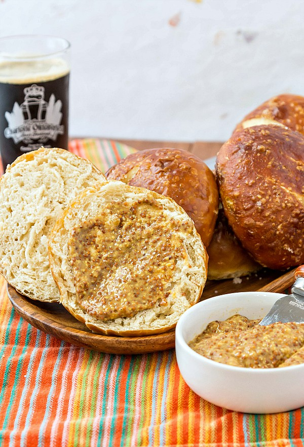 A wooden platter of pretzel buns. One is split open and slathered with whole grain mustard. A glass of dark beer is in the background.