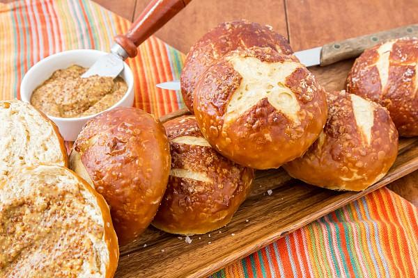 A wooden platter of baked pretzel buns. Ready for serving.
