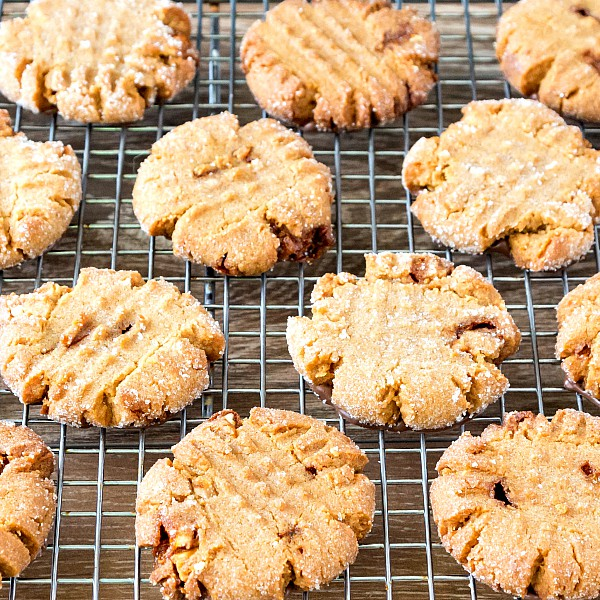 Overhead view of sugar-coated peanut butter cookies with familiar cross hatch design, on a cooling rack.