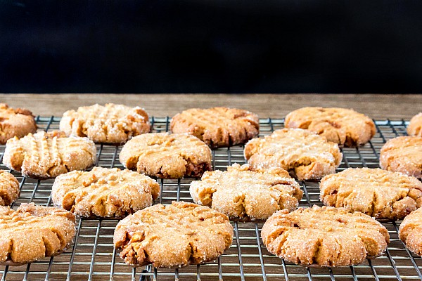 A cooling rack of triple peanut butter cookies cooling on a wooden surface.