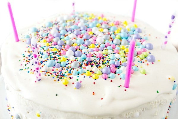 the top of an ice cream cake decorated with edible pearls and sprinkles and birthday candles