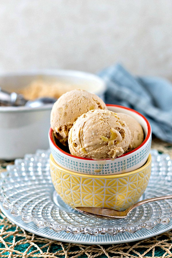 A bowl of scoops of Smoked Caramel Pineapple Ice Cream on a clear glass plate with silver spoon.