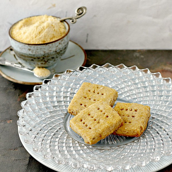 3 pieces of walnut shortbread on a plate with a bowl of toasted sugar in the background.