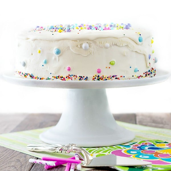a white iced ice cream cake on a white pedestal with birthday napkins and candles