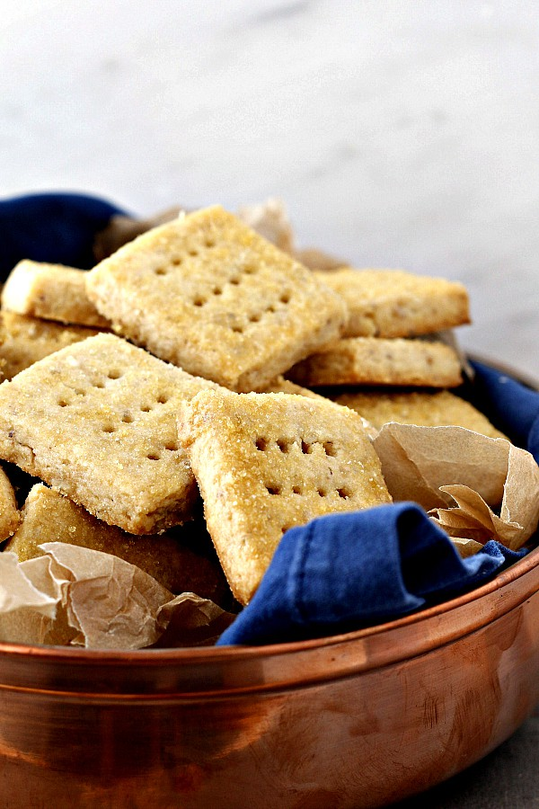 A container of square shortbread cookies with little holes pricked in them.