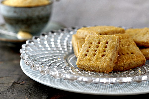 A clear glass plate of walnut shortbread cookies.