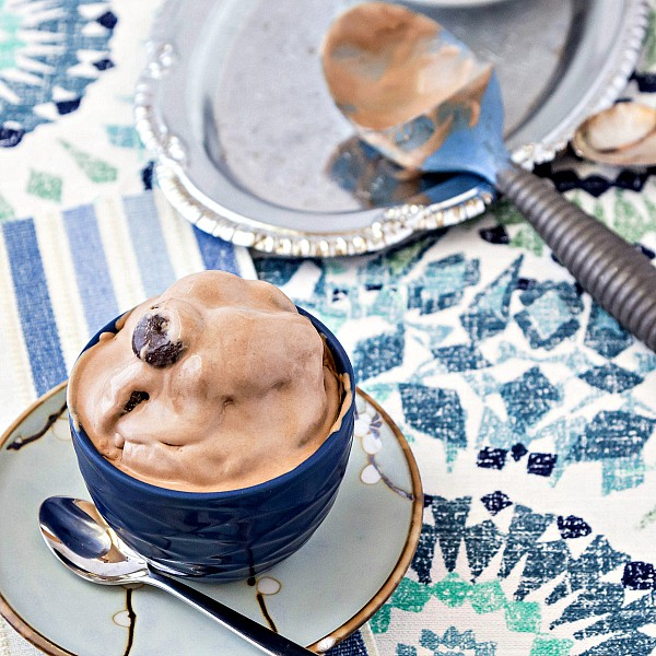 A bowl and spoon of Junior Mint Chocolate Ice Cream on a blue, white and green table cloth.