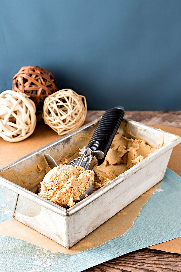 Metal loaf shaped container of homemade caramel vanilla ice cream with an ice cream scoop.