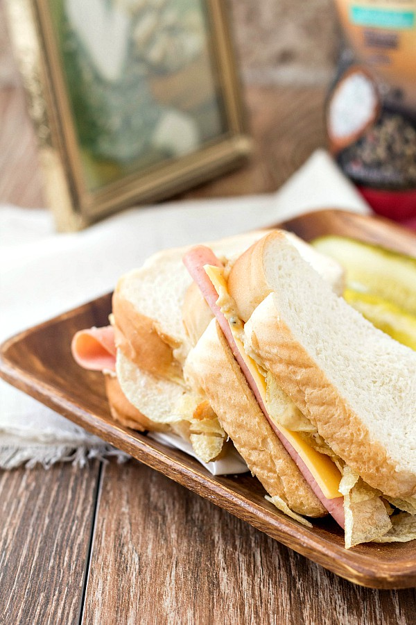 A bologna and cheese sandwich cut in half on a wooden plate with pickle spears.