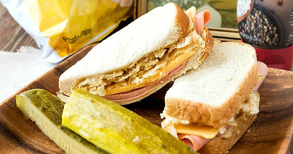 A cut bologna and cheese sandwich with pickle spears.